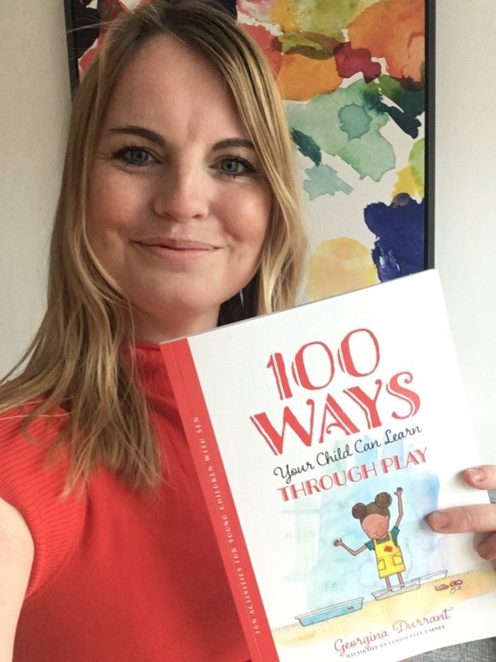 Woman holding book with 100 fun activities for children